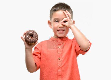 Fillette aux cheveux sombre manger en anneau avec le visage heureux souriant faisant signe OK avec la main sur les yeux regardant à travers les doigts
