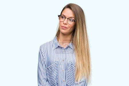 Beautiful young woman wearing elegant shirt and glasses smiling looking side and staring away thinking.