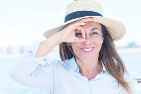 Beautiful middle age woman traveling on sailboat with happy face smiling doing ok sign with hand on eye looking through fingers