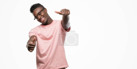 Young african american man wearing pink t-shirt approving doing positive gesture with hand, thumbs up smiling and happy for success. Looking at the camera, winner gesture.