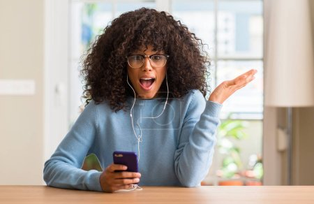 Beautiful african american woman using smartphone very happy and excited, winner expression celebrating victory screaming with big smile and raised hands
