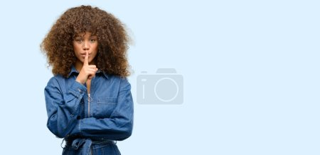 African american woman wearing blue jumpsuit with index finger on lips, ask to be quiet. Silence and secret concept