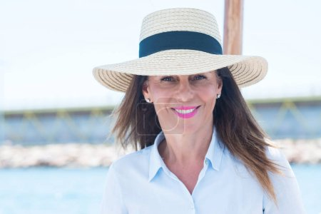 Photo for Beautiful middle age woman traveling on sailboat and smiling happy and confident. - Royalty Free Image