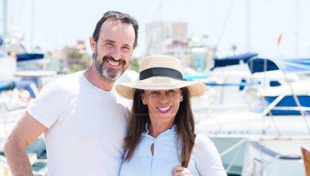 Photo pour Couple d'âge moyen dans la marina avec un visage heureux debout et souriant avec un sourire confiant montrant les dents - image libre de droit