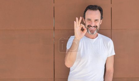 Handsome senior man standing over wall doing ok sign with fingers, excellent symbol