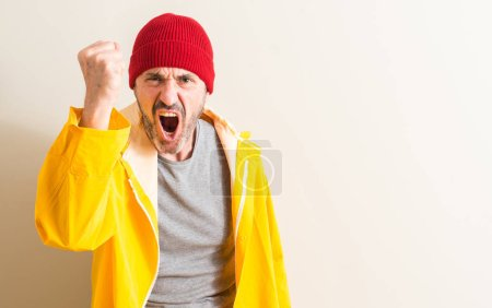 Senior fisherman annoyed and frustrated shouting with anger, crazy and yelling with raised hand, anger concept