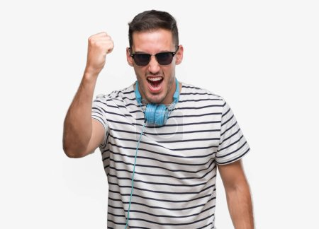 Handsome young man wearing headphones angry and mad raising fist frustrated and furious while shouting with anger. Rage and aggressive concept.