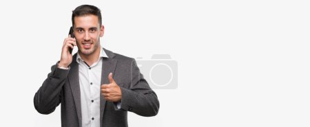Handsome young man using smartphone happy with big smile doing ok sign, thumb up with fingers, excellent sign