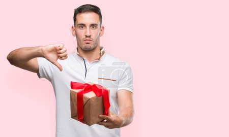Beau jeune homme qui donne un cadeau avec le visage en colère, signe négatif montrant n'aime pas avec les pouces vers le bas, notion de rejet