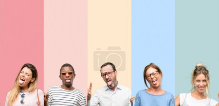 Photo for Mixed group of people, women and men looking at camera showing tongue and making victory sign with fingers - Royalty Free Image