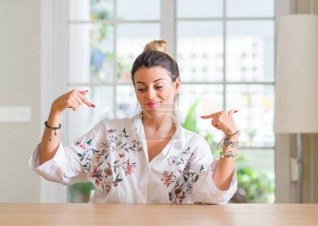 Photo pour Jeune femme à la maison regardant confiant avec le sourire sur le visage, se montrant du doigt fier et heureux . - image libre de droit