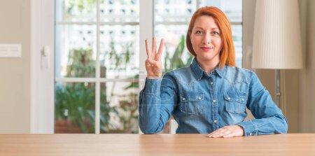Femme rousse à la maison montrant et pointant vers le haut avec le nombre de doigts trois en souriant, confiant et heureux