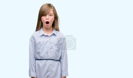 Young blonde toddler wearing blue shirt scared in shock with a surprise face, afraid and excited with fear expression