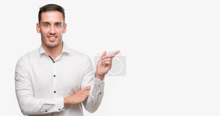 Photo for Handsome young business man very happy pointing with hand and finger to the side - Royalty Free Image