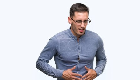 Handsome young elegant man wearing glasses with hand on stomach because indigestion, painful illness feeling unwell. Ache concept.