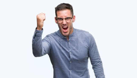 Handsome young elegant man wearing glasses angry and mad raising fist frustrated and furious while shouting with anger. Rage and aggressive concept.