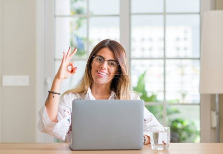 Young woman at home using laptop doing ok sign with fingers, excellent symbol