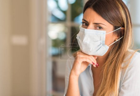 Photo for Beautiful young woman wearing contamination mask at home. Pollution and illness concept. - Royalty Free Image
