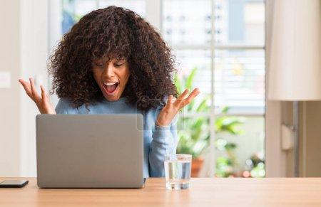 Photo pour Femme afro-américaine à l'aide d'ordinateur portable à la maison très heureux et excité, expression gagnant célébrant la victoire criant avec grand sourire et déclenché des mains - image libre de droit