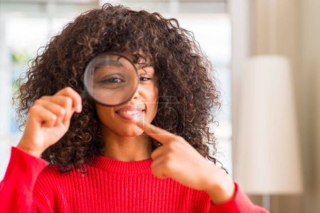 Curious african american woman looking through magnifying glass very happy pointing with hand and finger