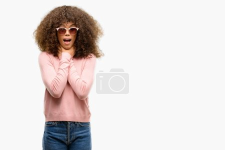 African american woman wearing pink sunglasses shouting and suffocate because painful strangle. Health problem. Asphyxiate and suicide concept.