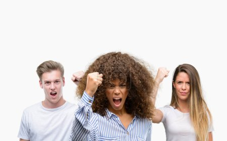 Group of young people over white background annoyed and frustrated shouting with anger, crazy and yelling with raised hand, anger concept