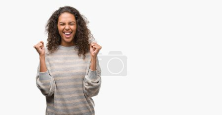 Beautiful young hispanic woman wearing stripes sweater excited for success with arms raised celebrating victory smiling. Winner concept.