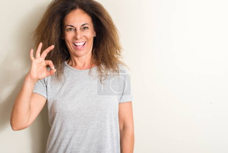 Curled hair brazilian woman doing ok sign with fingers, excellent symbol