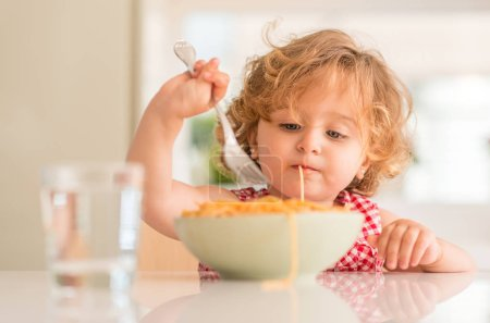 Beautiful blond child eating spaghetti
