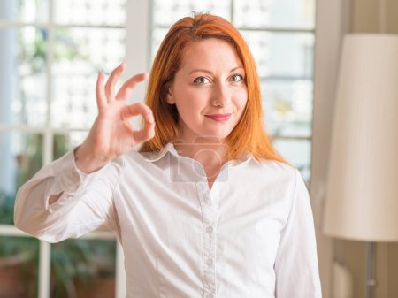 Redhead woman wearing white shirt at home doing ok sign with fingers, excellent symbol
