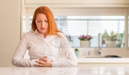 Redhead woman at kitchen with hand on stomach because indigestion, painful illness feeling unwell. Ache concept.