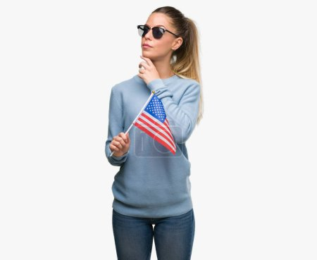 Photo pour Belle jeune femme tenant le drapeau Usa visage grave, penser à la question, très confuse idée - image libre de droit