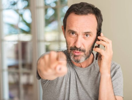 Photo for Middle age man using smartphone pointing with finger to the camera and to you, hand sign, positive and confident gesture from the front - Royalty Free Image