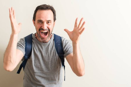 Photo for Senior man using backpack very happy and excited, winner expression celebrating victory screaming with big smile and raised hands - Royalty Free Image
