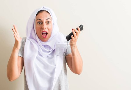 Photo for Arabian woman using smartphone very happy and excited, winner expression celebrating victory screaming with big smile and raised hands - Royalty Free Image