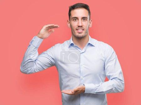 Photo pour Beau jeune homme d'affaires geste avec les mains montrant grand et grand signe de taille, symbole de mesure. Souriant en regardant la caméra. Concept de mesure. - image libre de droit