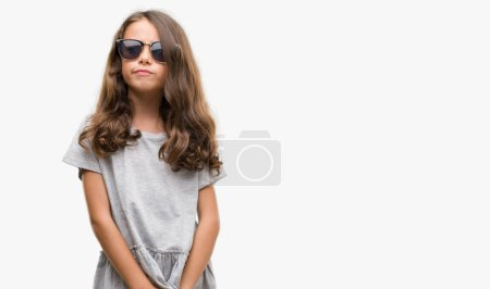 Brunette hispanic girl wearing sunglasses smiling looking side and staring away thinking.