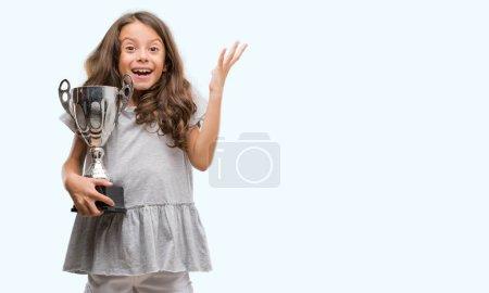 Photo pour Brunette hispanique fille tenant un trophée très heureux et excité, expression gagnante célébrant la victoire en criant avec un grand sourire et les mains levées - image libre de droit