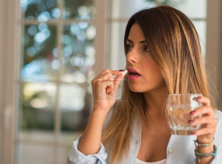 Beautiful young woman taking a pill while drinking a glass of water. Illness concept.