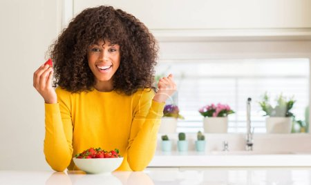 Photo for African american woman eating strawberries at home screaming proud and celebrating victory and success very excited, cheering emotion - Royalty Free Image