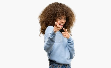 African american woman wearing a sweater pointing fingers to camera with happy and funny face. Good energy and vibes.