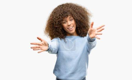 Photo pour Femme afro-américaine portant un pull regardant la caméra souriant à bras ouverts pour un câlin. Expression joyeuse embrassant le bonheur . - image libre de droit