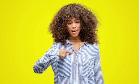Photo pour Femme afro-américaine portant une chemise à rayures avec visage surprise pointant du doigt vers lui-même - image libre de droit