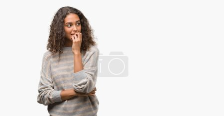 Photo for Beautiful young hispanic woman wearing stripes sweater looking stressed and nervous with hands on mouth biting nails. Anxiety problem. - Royalty Free Image
