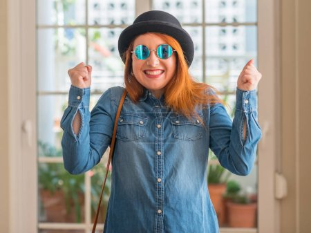 Photo for Stylish redhead woman wearing bowler hat and sunglasses excited for success with arms raised celebrating victory smiling. Winner concept. - Royalty Free Image
