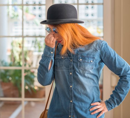 Stylish redhead woman wearing bowler hat and sunglasses tired rubbing nose and eyes feeling fatigue and headache. Stress and frustration concept.