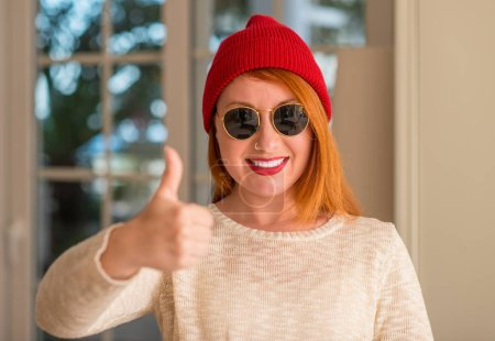 Stylish redhead woman wearing wool cap and sunglasses happy with big smile doing ok sign, thumb up with fingers, excellent sign