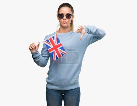 Belle jeune femme tenant le drapeau du Royaume-Uni avec visage en colère, signe négatif montrant n'aime pas avec les pouces vers le bas, notion de rejet