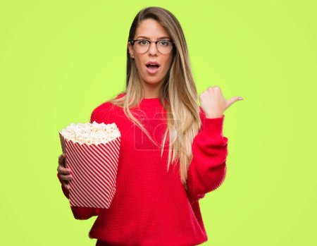 Beautiful young woman eating popcorn pointing with hand and finger up with happy face smiling