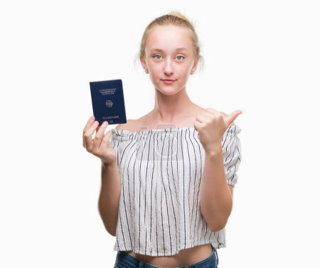 Photo pour Femme blonde adolescent détenteurs d'un passeport de l'Allemagne de pointage et montrant avec le pouce jusqu'à la face visage heureux souriant - image libre de droit